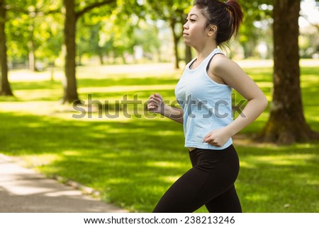 Healthy and beautiful young woman jogging in park