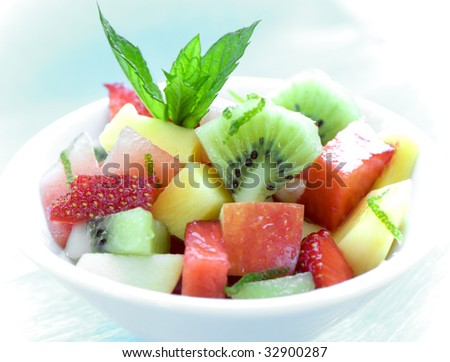 healthy and deliciously looking bowl of fruit salad on blue background - stock photo