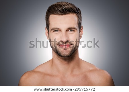Healthy and handsome. Portrait of handsome young shirtless man looking at camera and smiling while standing against grey background - stock photo