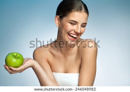 Healthy and Happy, natural organic raw fresh food concept / portrait of attractive smiling girl with green apple in her hand over blue background  - stock photo