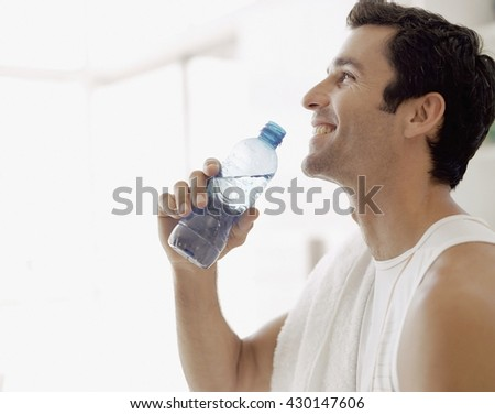 Healthy and happy young man drinking water while relaxing at home - stock photo
