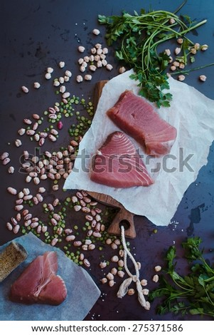 Healthy and local food concept. Tuna steak and dried vegetables over dark background.  - stock photo