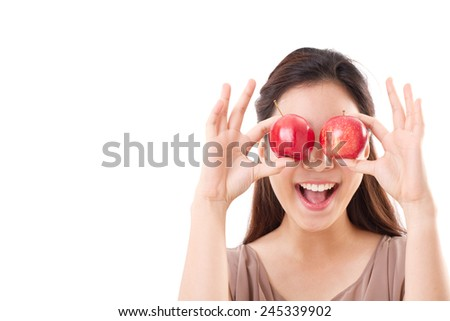 healthy and playful woman covering her eyes with two red apples, brown dress for summer and spring season - stock photo