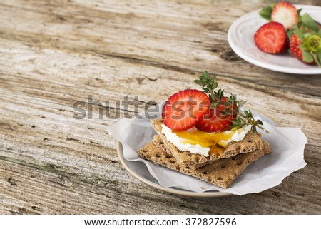 Healthy and tasty breakfast cereal crispy bread roll with curd cheese, strawberries, honey and thyme on a wooden table - stock photo