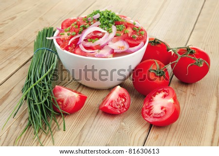 healthy appetizer : fresh tomato salad in white bowl with bunch of chives and raw tomatoes on twig , violet onion, over wooden table - stock photo