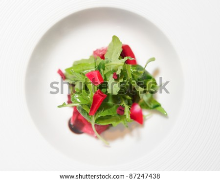Healthy appetizer of ruccola, rose petals and delicious topping in white plate - stock photo