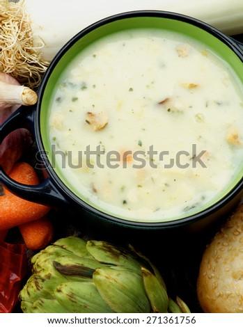 Healthy Artichoke Creamy Soup with Raw Leek, Carrot, Garlic and Cheese in Dark Blue Pannikin closeup. Top View - stock photo