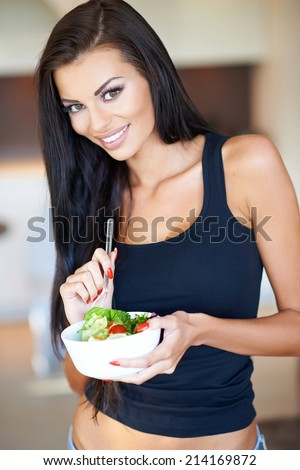 Healthy attractive slender woman eating a fresh mixed salad from a handheld bowl indoors at home looking at the camera with a friendly smile - stock photo