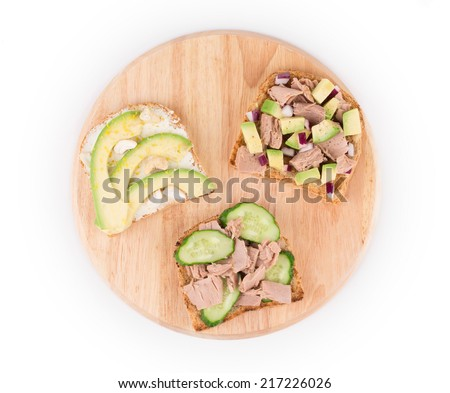 Healthy avocado sandwich on wood platter. Isolated on a white background.