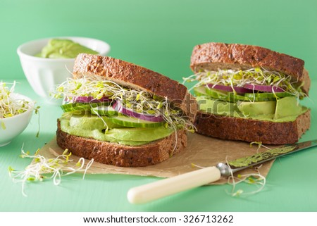 healthy avocado sandwich with cucumber alfalfa sprouts onion - stock photo