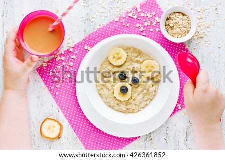 Healthy baby breakfast - oatmeal porridge with fruit. Morning diet concept for children. Fun food idea for kids - stock photo