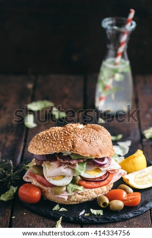Healthy bagel sandwich with turkey breast and eggs served on wooden background,selective focus - stock photo