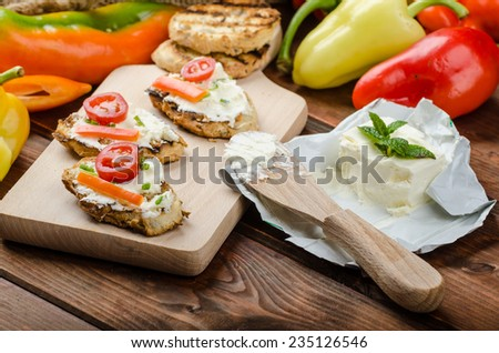 Healthy baguette, spread curd cheese with vegetable and herbs, variations of peppers - stock photo