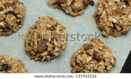 Healthy Banana Oatmeal Cookies on White Plate on Wooden Table - Vegan cookies made of banana, oatmeal, nuts, roasted oat grains, linseed, raisens and chia seeds