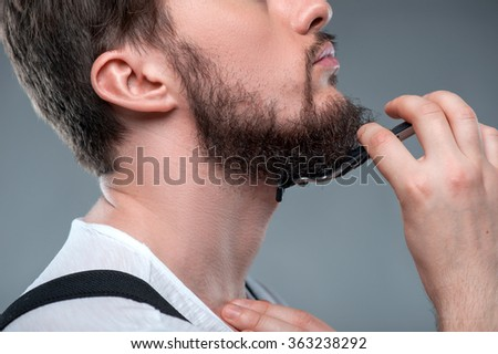 Healthy bearded young guy with sharp razor - stock photo