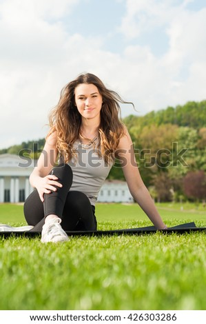 Healthy beautiful woman practicing pilates in the nature as balance and wellness concept - stock photo