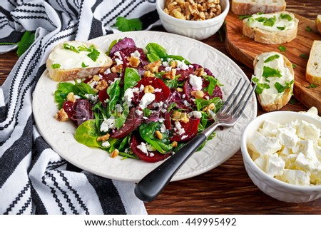 Healthy Beet Salad with fresh sweet baby spinach, kale lettuce, nuts, feta cheese and toast with melted cheese - stock photo