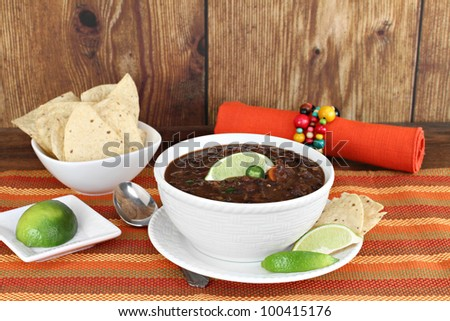Healthy black bean mexican soup with lime and tortilla chips. - stock photo