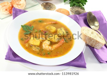 healthy bouillabaisse with seafood and parsley on a bright background - stock photo