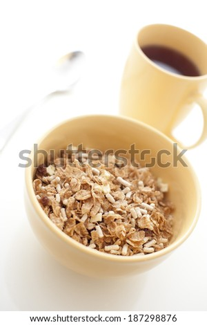 Healthy bowl of muesli breakfast cereal served with mug of aromatic hot espresso coffee for an energising start to the day - stock photo