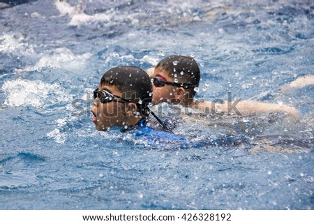 healthy boy butterfly swims in swimming pool , Asian young kid training with swim goggles - stock photo