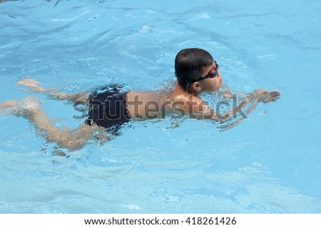 healthy boy front crawl swims in swimming pool , Asian young kid training with swim goggles - stock photo