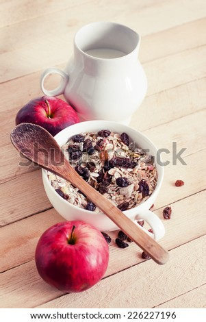 healthy breakfast background/ Bowl of oat flake with raisins, milk and apples on wooden background - health and diet concept - stock photo