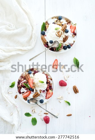Healthy breakfast. Berry crumble with fresh blueberries, raspberries, strawberries, almond, walnuts, pecans, yogurt, and mint in ceramic plates over white wooden surface. Top view - stock photo