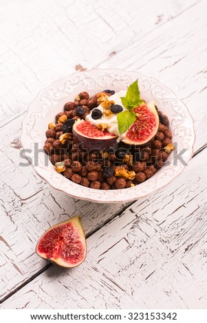Healthy breakfast: bowl of chocolate balls with yoghurt and fresh figs on white wooden table. Selective focus - stock photo