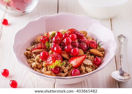 Healthy breakfast - bowl of oat granola with fresh fruit, almond and white chocolate, selective focus. - stock photo