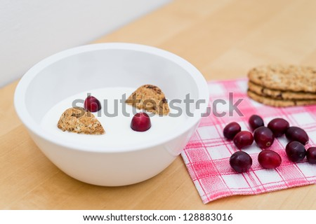 Healthy breakfast containing natural yogurt, wholemeal cereal biscuits and fresh cranberries