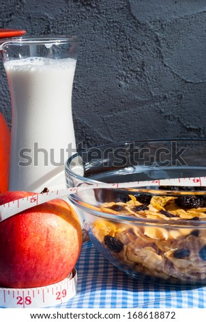 healthy breakfast: cornflakes , Apples ,  raisin with milk on the wooden table