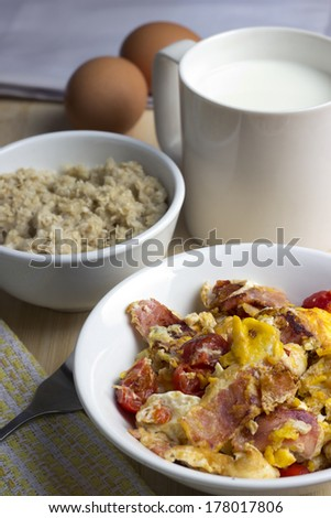 Healthy breakfast: eggs with bacon, oatmeal and milk - stock photo