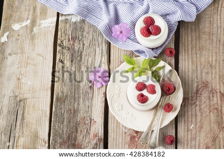 Healthy breakfast for two fresh batch of yogurt with juicy ripe raspberries. Served in a rustic wooden background. selective focus - stock photo