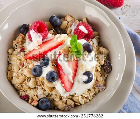 Healthy Breakfast - fresh berries, yogurt and  muesli. Selective focus - stock photo