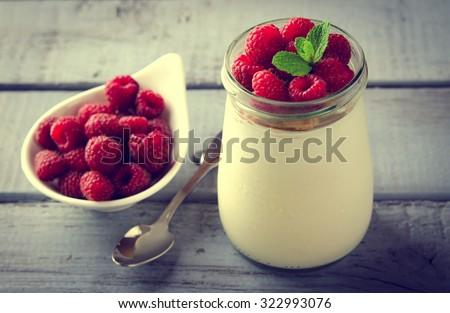 Healthy breakfast - fresh Greek yogurt with raspberries and mint in a glass - stock photo