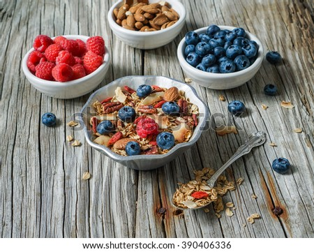 Healthy breakfast. Fresh homemade coconut granola, muesli in a glass jar. Organic oats, almond, pecans, berries and goji berries. Selective focus. - stock photo