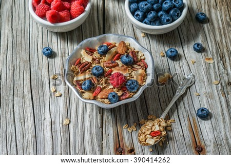 Healthy breakfast. Fresh homemade coconut granola, muesli in a glass jar. Organic oats, almond, pecans, berries and goji berries. Selective focus. Close up. - stock photo