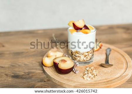 healthy breakfast: granola, cereal, yogurt with peach and plum - stock photo