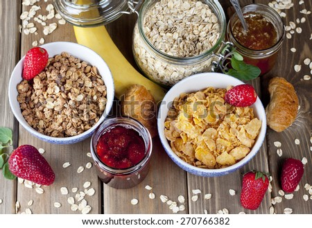 Healthy breakfast including flakes, muesli, honey, berries, jam