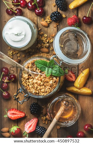 Healthy breakfast ingredients. Oat granola in open jar, yogurt and honey served with berries, nuts and fresh mint on rustin wooden background. Top view, vertical composition - stock photo
