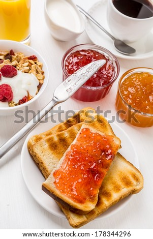 Healthy Breakfast Meal - Toasts with Jam, Bowl of Fruit, Oat and Nut Granola  with Yogurt and Raspberries - stock photo
