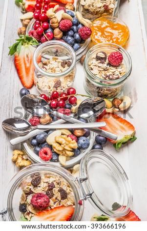 Healthy breakfast muesli bar. Muesli in jar with fresh berries, seeds and  nuts - stock photo