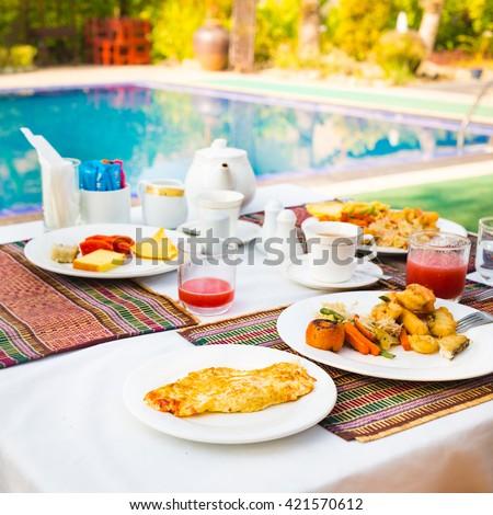 Healthy breakfast near a swimming pool - stock photo