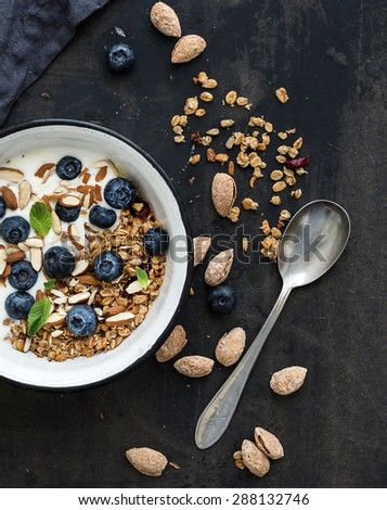 Healthy breakfast. Oat granola with fresh blueberries, almond, yogurt and mint in a rustic metal bowl over dark grunge surface. Top view - stock photo