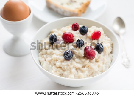 Healthy breakfast: oatmeal porridge with blueberries and cranberries topped with granola in white bowl, hard boiled egg in white egg cup and slice of raisin cake on white plate. Selective focus - stock photo