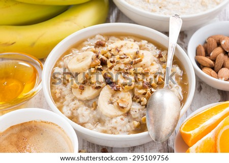 healthy breakfast - oatmeal with banana, honey and walnuts in bowl, top view, horizontal - stock photo