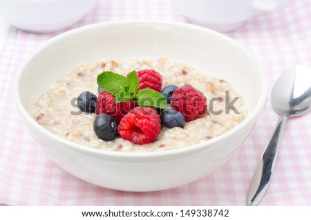 healthy breakfast - oatmeal with fresh berries in a bowl, horizontal closeup - stock photo