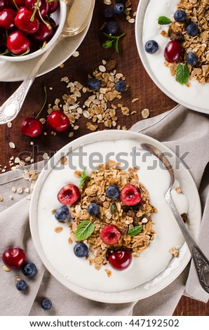 Healthy breakfast of homemade granola with yogurt and berries on rustic background