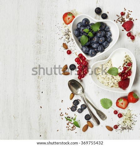 Healthy breakfast of muesli, berries with yogurt and seeds on white background -  Healthy food, Diet, Detox, Clean Eating or Vegetarian concept. - stock photo